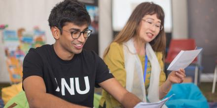 ANU anthropology PhD candidate, Dinith Adikari (left), and Burmese program convenor, Dr Yuri Takahashi, take part in a bilingual storytelling activity at the Canberra Moon Festival on 26 September 2018.